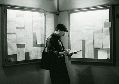 Stanley Roseman noting the schedule of rehearsals, performances, and changes of cast listed on the bulletin boards in a backstage corridor of the Palais Garnier. Photo by Ronald Davis.