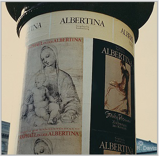 "At the entrance to the Albertina, Vienna, the column displaying the posters announcing the museum's exhibitions ""Raphael in der Albertina"" and ""Stanley Roseman - Zeichnungen aus Klostern,"" 1983. Photo © Ronald Davis"