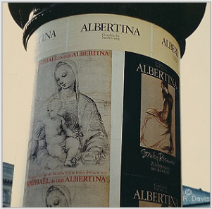 "At the entrance to the Albertina, Vienna, the column displaying the posters announcing the museum's exhibitions ""Raphael in der Albertina"" and ""Stanley Roseman - Zeichnungen aus Klostern,"" 1983. Photo by Ronald Davis."